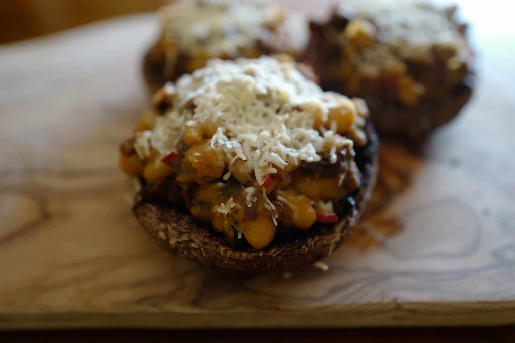 Close up stuffed portobello vegetarian cap filled with sun-dried tomatoes, sprinkled with Pecorino cheese, by Foodjoya