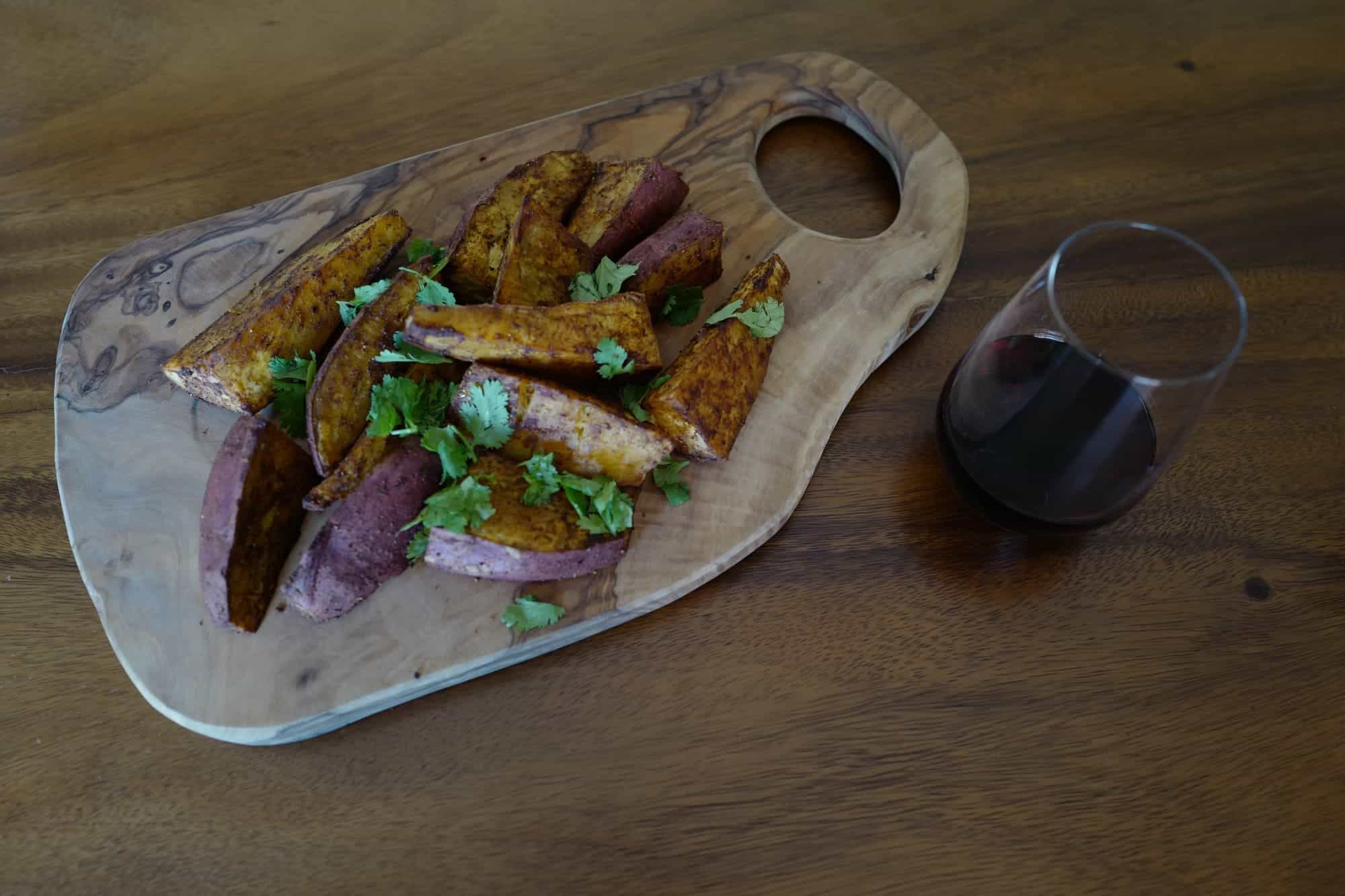 Roasted Japanese sweet potato wedges with spices on a wooden board next to a glass of red wine by Foodjoya