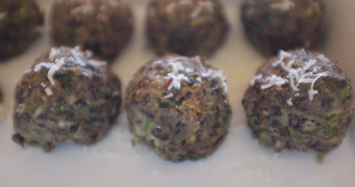 Beluga lentil meatballs, vegetarian, arranged in a row, by Foodjoya