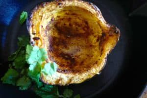 Roasted acorn squash (winter squash) with spices, avocado oil, served next to cilantro and mint by Foodjoya.