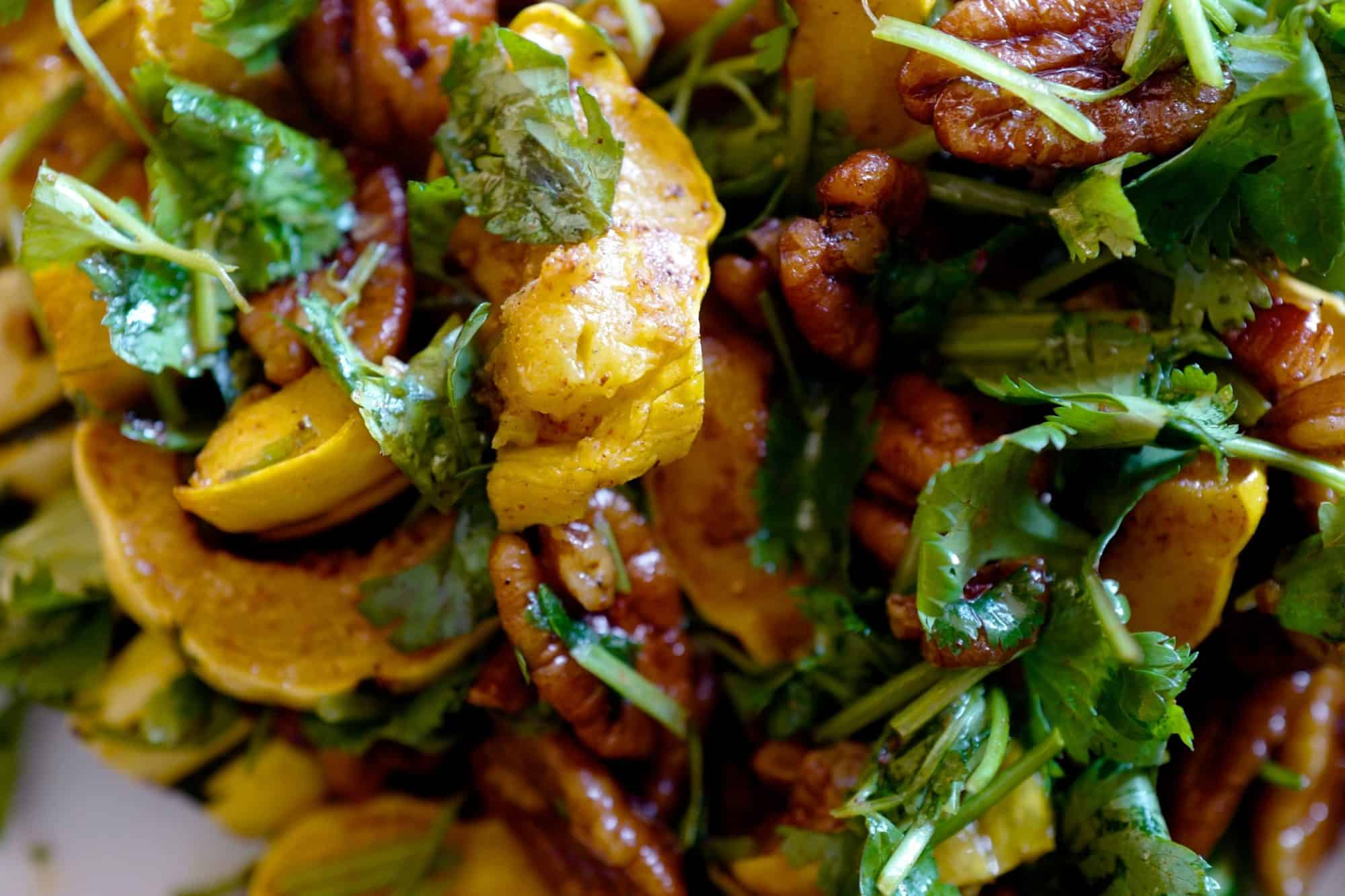 Delicata squash salad with herbs and spicy pecans close up by foodjoya