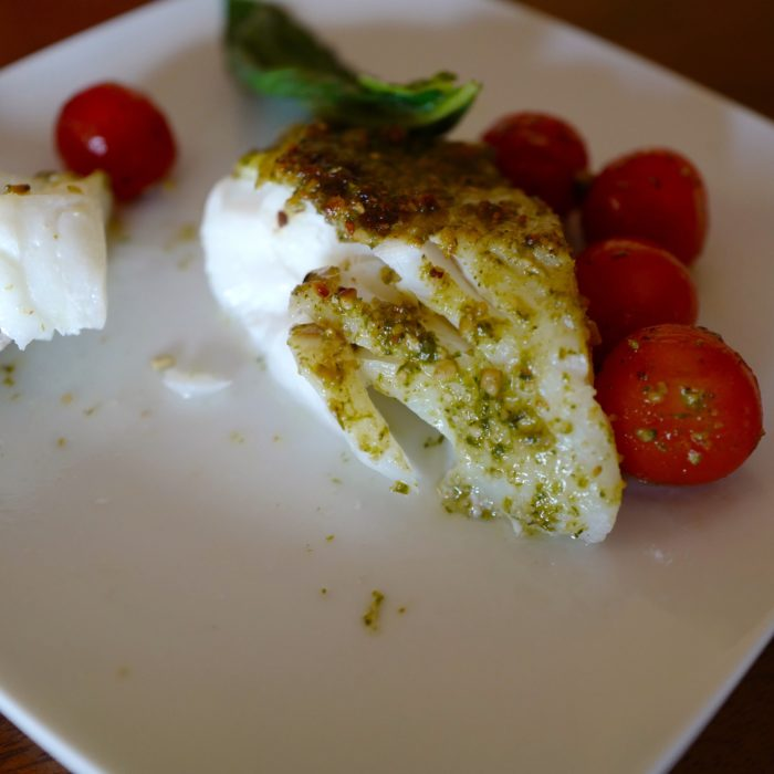Pesto baked cod cut with a fork by foodjoya